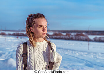 Beautiful woman in white sweater in winter on street at the weekend, resting looks into the distance, free space for text. White mittens. Background of the river is snow and drifts.