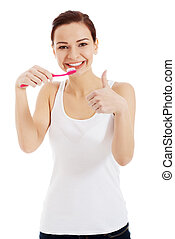 Beautiful woman in white top is brushing her teeth.