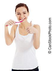 Beautiful woman in white top is brushing her teeth.