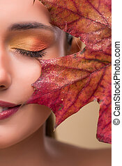 Beautiful woman in with autumn dry leaves