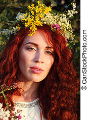 Beautiful woman in wreath with bunch of flowers at summer sunny day