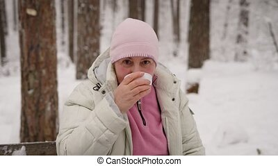 Beautiful woman in years enjoying her leisure time in winter forest sitting on the wooden bench at the table. Happy retired lady is spending her holiday in outdoors drinking hot tea from white cup.