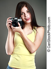 beautiful woman in yellow with a camera, emotions