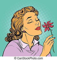 Beautiful woman inhaling fragrance of a flower