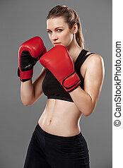 beautiful woman is boxing on gray background - beautiful...