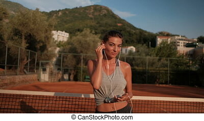 Beautiful woman is dancing with headphones on a tennis court...