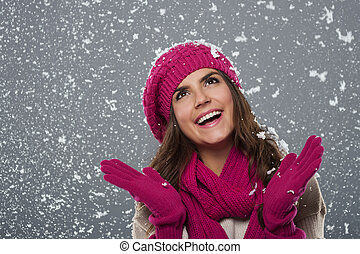 Beautiful woman is happy from snow in winter time