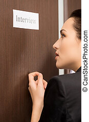Beautiful woman is knocking to the door. Getting ready for interview