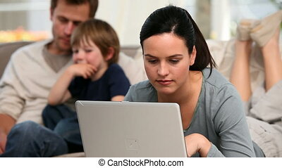 Beautiful woman is on her laptop while her family is on a sofa