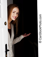 Beautiful smiling woman is opening door and inviting to come in.