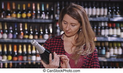 Beautiful woman is standing and reading label of champagne...