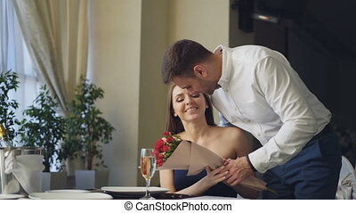 Beautiful woman is waiting for her boyfriend in restaurant, he is coming and giving her flowers, kissing her. Happy girl is smelling flowers and smiling with pleasure.