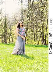 Beautiful woman is walking in a meadow