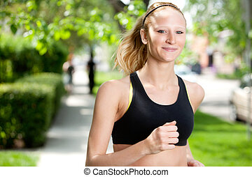 Beautiful woman jogging - Portrait of a young woman smiling...