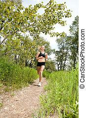 Beautiful woman jogging - Young woman jogging outdoors in...