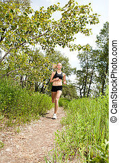 Beautiful woman jogging - Young woman jogging outdoors in...