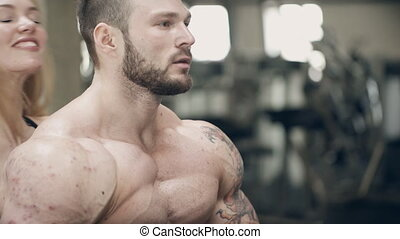 Beautiful woman kisses behind the ear, bodybuilder and they...