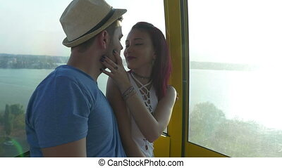 Beautiful woman kissing her boyfriend in cableway at the seaside