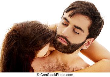 Beautiful woman kissing man's neck.