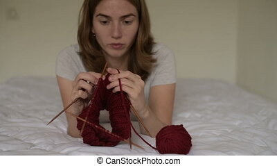 Beautiful woman knitting on a bed