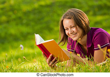 Beautiful woman laughing with a book in the park