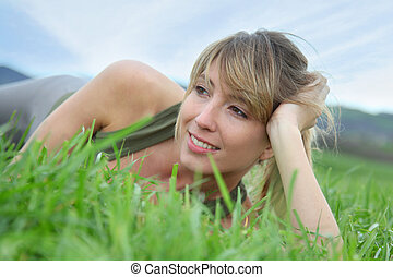 Beautiful woman laying down green field