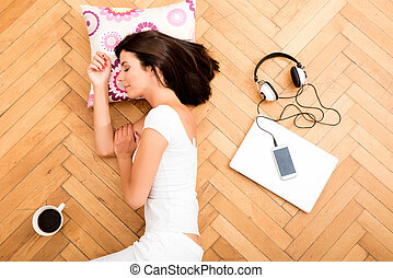 Beautiful woman laying on the floor with a laptop, smartphone, coffee, and headphones around her