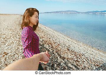 Beautiful woman leading man on beach near the sea