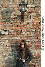 Beautiful woman leaned against brick wall