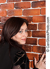 Beautiful woman leaning against brick wall