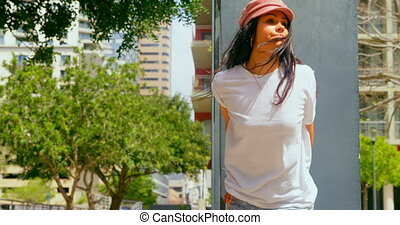 Beautiful woman leaning on pillar in the city. City in the background 4k