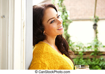 Beautiful woman leaning on wall and holding drink