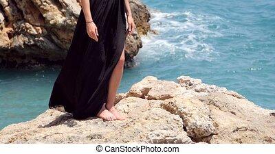 Beautiful woman legs in elegant black dress near the sea