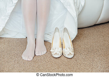 Beautiful woman legs in whitel shoes. Wedding dress and shoes. Morning of the bride.