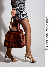 Beautiful woman legs with a brown bag