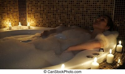beautiful woman lies in a bubble bath by candlelight.