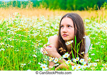 beautiful woman lies in a green field with flowers