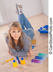 beautiful woman lies on wooden floor holding single paintbrush and looking at camera