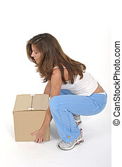 Beautiful attractive woman squatting and lifting a small plain brown box with her knees bent.