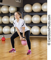 Beautiful Woman Lifting Kettlebell In Health Club