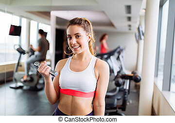 Beautiful woman lifting weights in gym