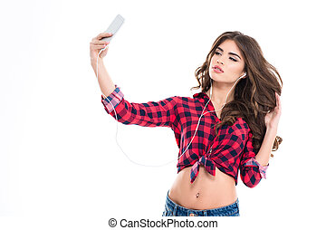 Beautiful woman listening to music and making selfie with...