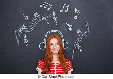 Beautiful woman listening to music in earphones drawn on...