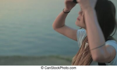 Beautiful woman listening to music in roller skates on the seashore 4k