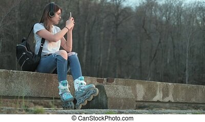 Beautiful woman listening to music in roller skates on the seashore