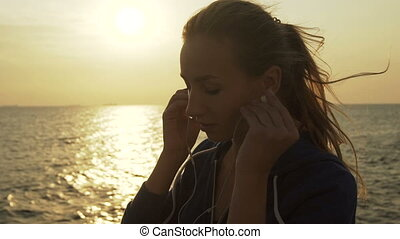 Beautiful woman listening to music near the sea.