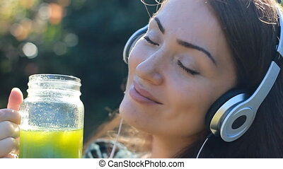 Beautiful woman listening to music with headphones and...