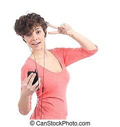 Beautiful woman listening to the music with headphones and dancing