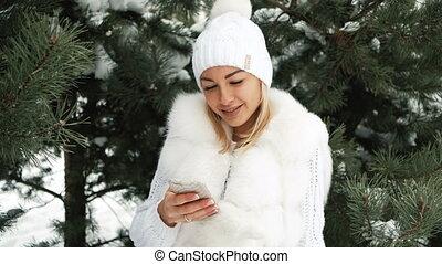 Beautiful woman listens to music in earphones, winter landscape.