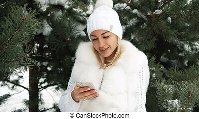 Beautiful woman listens to music in earphones, winter...